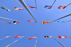 Bandeiras nacionais e fundo diferentes do céu Imagens de Stock Royalty Free