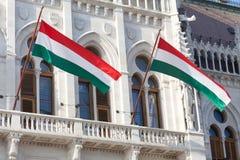 Bandeiras nacionais húngaras na construção húngara do parlamento imagem de stock