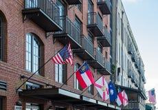 Bandeiras no hotel velho do tijolo Imagem de Stock
