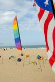 Bandeiras, peúgas de vento e papagaios na praia fotografia de stock royalty free
