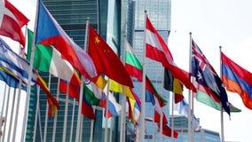 Bandeiras que acenam perto do prédio de escritórios moderno filme
