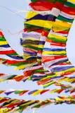 Bandeiras tibetanas budistas da oração contra o céu azul imagens de stock