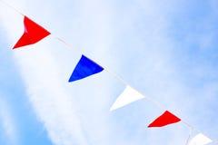 Bandeiras vermelhas, azuis e brancas contra um céu azul Imagem de Stock