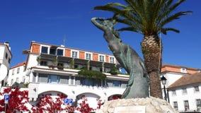 A bandeja acima de uma estátua da sereia com construções branco-lavadas cobriu o fundo colorido das flores, Cascais, Portugal filme