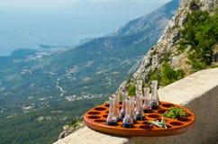 Bandeja com as garrafas de vinho e salsa pequenas na frente dos montes e rochas da cordilheira de Biokovo e do mar de adriático d fotos de stock royalty free