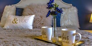 Bandeja com canecas e vaso de flor sobre uma cama imagem de stock