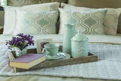Bandeja com livro, grupo de chá e flor na cama Imagem de Stock