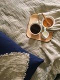 bandeja com mel e um copo do chá quente na cama, manhã preguiçosa, tampa de linho do humor morno do inverno imagem de stock