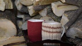 Bandeja com os dois copos da bebida quente, em uma pilha de madeira filme