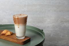 Bandeja com vidro do macchiato do caramelo e pastelaria saboroso na tabela imagem de stock