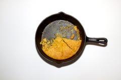 Bandeja comida metade do cornbread em um skillett do ferro fundido isolado sobre Imagem de Stock