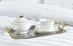 Bandeja con el cuenco de la taza y de azúcar en una cama Imagenes de archivo