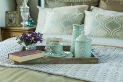 Bandeja con el libro, el juego de té y la flor en la cama Foto de archivo