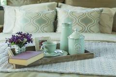 Bandeja con el libro, el juego de té y la flor en la cama Imagen de archivo