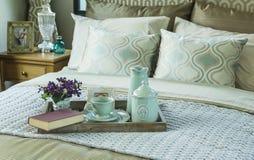 Bandeja con el libro, el juego de té y la flor en la cama Imagenes de archivo