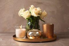 Bandeja con las velas y las flores ardiendo de la cera fotografía de archivo libre de regalías