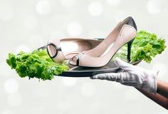 Bandeja con pares de zapatos femeninos en las manos del camarero Fotografía de archivo