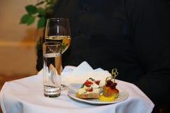 Bandeja, cubierta con un mantel blanco, con un vidrio de vino, takan con agua y una placa de bocados en la mano del camarero Imagen de archivo