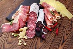 Bandeja da carne da guloseima de jamon e de fuet empurrado da salsicha em uma tabela de madeira imagens de stock