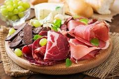 Bandeja da restauração do Antipasto com bacon, espasmódico, salsicha, queijo azul e uvas foto de stock royalty free