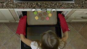 Bandeja da tomada da menina com as cookies do gengibre do biscoito do forno Vista à parte superior e sorriso Mitenes vermelhos em filme