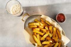 Bandeja de batatas fritas caseiros com ketchup e cerveja escura Imagens de Stock Royalty Free