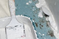 Bandeja de la brocha y de la pintura cubierta en la pintura blanca Fotografía de archivo libre de regalías