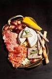 Bandeja de la comida con el surtido y el queso del charcuterie Imágenes de archivo libres de regalías