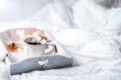 Bandeja de madera con el desayuno ligero en cama Fotos de archivo
