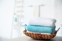 Bandeja de mimbre con las toallas en la tabla fotografía de archivo libre de regalías