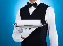 Bandeja de plata que lleva del camarero con la tarjeta en blanco Foto de archivo libre de regalías