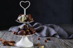 Bandeja de servicio de dos niveles blanca por completo de confitería dulce con los caramelos de chocolate y las almendras garapiñ imagen de archivo libre de regalías