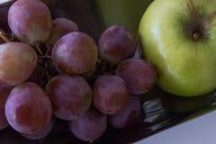 Bandeja de uvas con la manzana Foto de archivo