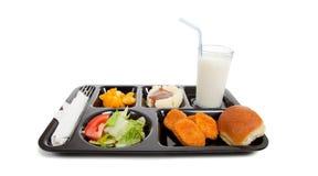 Bandeja del almuerzo de escuela con el alimento en un backgrounf blanco Foto de archivo