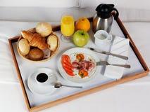 Bandeja del desayuno que pone en la cama blanca foto de archivo