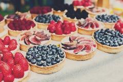 Bandeja del postre de las tartas de la fruta y de la baya clasificada al aire libre Fotografía de archivo libre de regalías