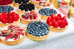 Bandeja del postre de las tartas de la fruta y de la baya clasificada al aire libre Foto de archivo
