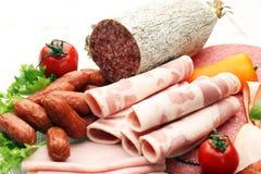 Bandeja do alimento com salame delicioso, partes de presunto cortado, salsicha, tomates, salada e vegetal - bandeja da carne com  Foto de Stock