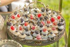Bandeja do bolinho de amêndoa do fruto e do creme com as bagas preparadas para o aniversário e o casamento em uma grande bandeja  foto de stock
