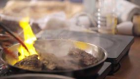 A bandeja do cozinheiro frita a carne O homem frita a carne na frigideira ardente Fogo em uma frigideira Fim acima Repreensão da  video estoque
