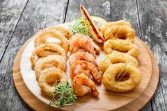 Bandeja do marisco com anéis do calamar, camarão fritado e os anéis de cebola decorados com o limão na placa de corte no fundo de Imagem de Stock Royalty Free