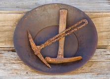 Bandeja do ouro que prende duas picaretas velhas da mineração Foto de Stock