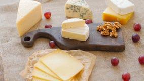 Bandeja do queijo com porcas e uvas em uma placa de corte de madeira video estoque