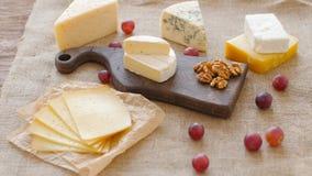 Bandeja do queijo com porcas e uvas em uma placa de corte de madeira filme