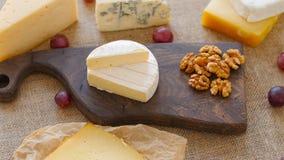 Bandeja do queijo com porcas e uvas em uma placa de corte de madeira vídeos de arquivo