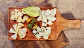 Bandeja do queijo decorada com mel e maçã Imagens de Stock Royalty Free