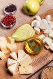Bandeja do queijo decorada com mel, maçã e especiaria Fotografia de Stock Royalty Free