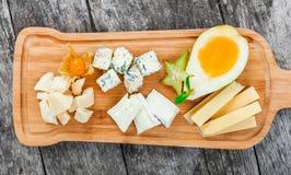 Bandeja do queijo decorada com pera, mel, nozes, uvas, carambola, physalis na placa de corte no fundo de madeira Fotografia de Stock Royalty Free
