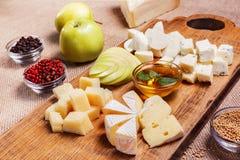Bandeja do queijo decorada na placa de madeira rústica Imagens de Stock