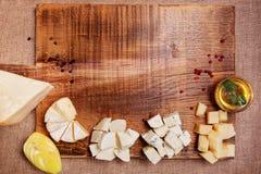 Bandeja do queijo decorada na placa de madeira rústica Foto de Stock